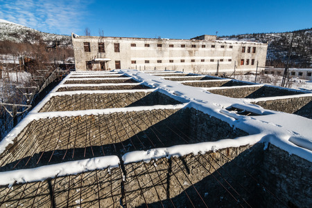 pokey: Exterior of buildings of old decayed abandoned prison in Kolyma in sunlight