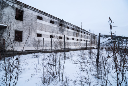 pokey: Exterior of housing of old decayed abandoned prison in Kolyma in sunlight Stock Photo
