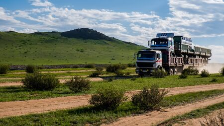Long truck carrying another long vehicle with van on the top on the gravel road in steppe