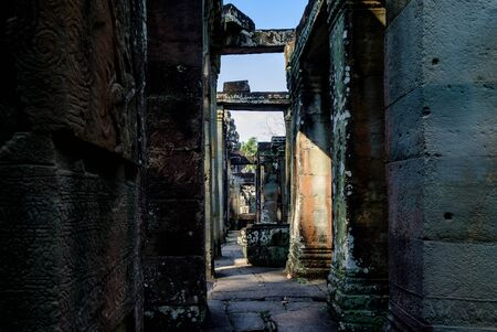 Narrow corridors in ruins of old ancient Angkor temple in Cambodia. Abstract architectural background.