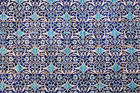 Maiolica style tin-glazed pottery tiled wall in ancient Khiva mosque in Uzbekistan. Abstract art background. Imagens