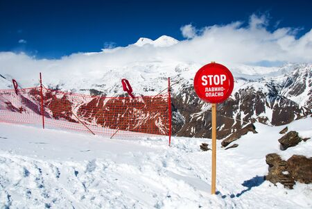 Avalanche warning sign and net fence in Caucasus mountains. Mount Elbrus ln background. Reklamní fotografie