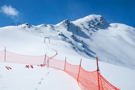 Avalanche warning sign and net fence in Caucasus mountains. Mount Cheget ln background. Reklamní fotografie