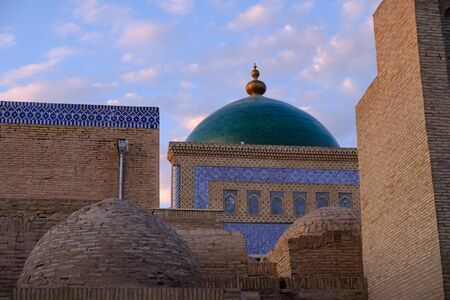 Roofs and cupolas of old town in sunset light, in Khiva, Uzbekistan. Central Asia travel view Banco de Imagens