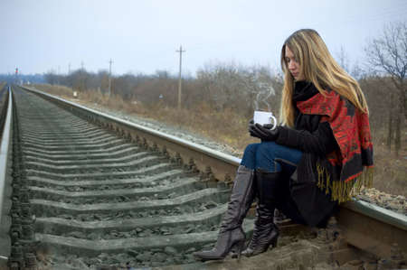 The girl sits on rails and holds a cup of hot tea photo
