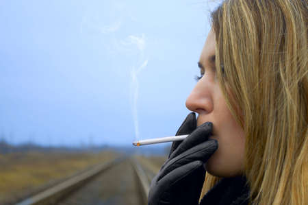 The girl smokes a cigaret against the railway photo