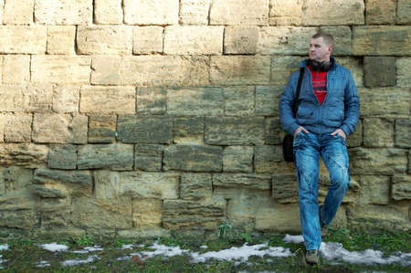 The guy with earphones stand near a brick wall Stock Photo - 8790349