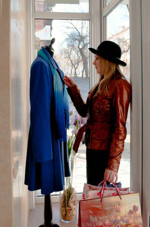 The girl in a hat and with bags selects a coat from shop photo