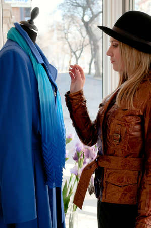 The girl in a hat selects a coat from shop photo