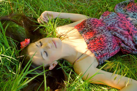 blindly: The young girl lies in a grass blindly