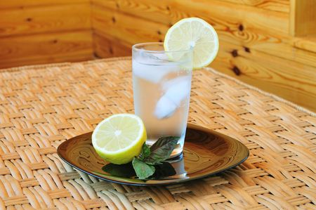 Glass of water with a lemon on the table photo