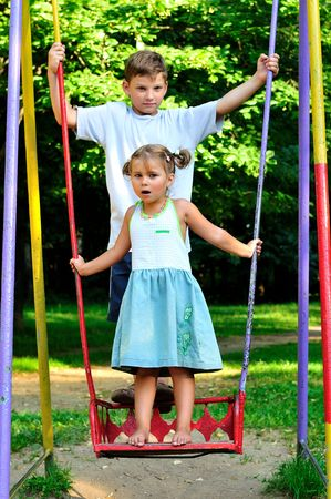 The boy and the girl on a swing in park photo