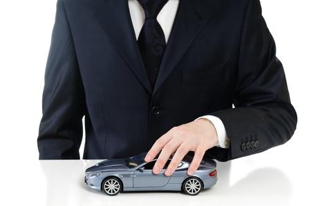dream car: hombre con un coche de juguete gris en la mano
