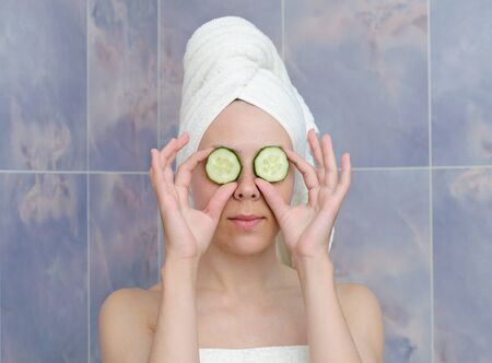 young woman with a cucumbers on eyes photo