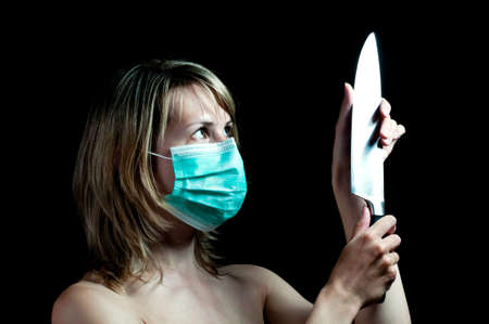 deranged: woman with a knife on dark background