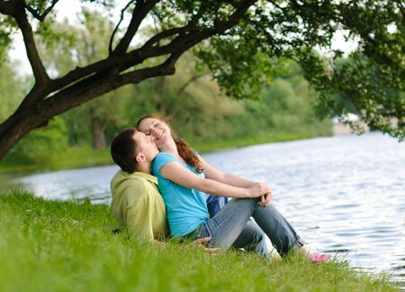 couple talking: adorable young woman and man in the park