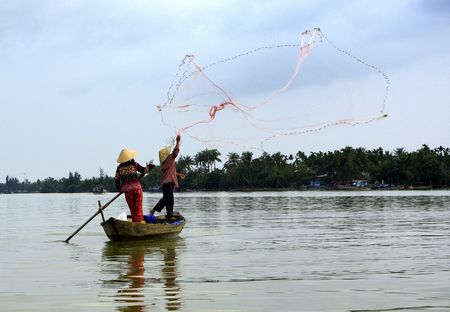 Two fishermen in action with their net in a little boat on the Mekong river