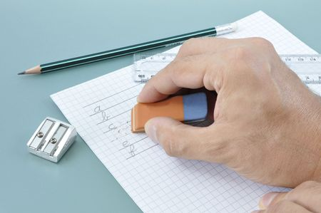 Hand erasing a writed mistake on a white paper during a writing exercise