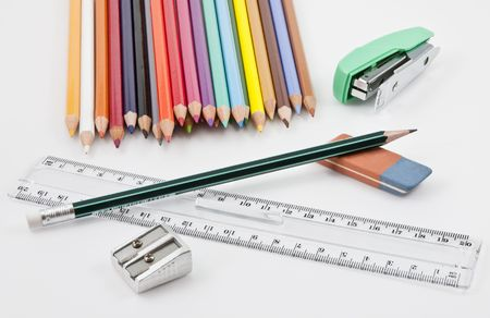 School supplies with colored pencils, pencil,  eraser, sharpener, stapler and plastic ruler Stock Photo