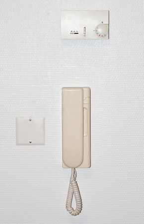 adjuster: Beige intercom on a white wall with an air conditioning adjuster