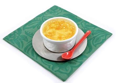 savour: Custard with a little red ceramic spoon on a green paper napkin and a white background