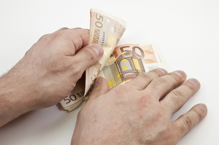 spendthrift: Two hands counting wad of fifty Euro banknotes Stock Photo