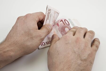 spendthrift: Two hands counting wad of ten Euro banknotes