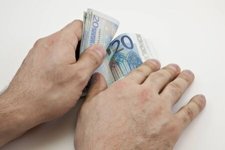 spendthrift: Two hands counting wad of twenty Euro banknotes Stock Photo