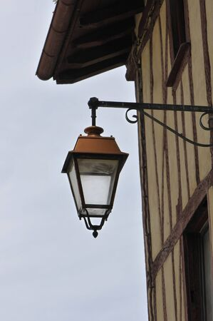 bask: Old style metallic lantern on a bask house wall with a cloudy sky