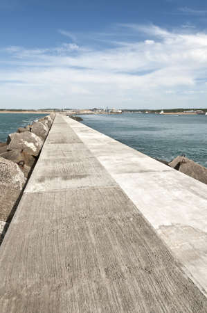 Long concrete jetty with quiet sea and blue sky Stock Photo