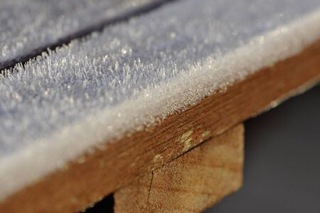 dept: Frost on brown wood table with a thin dept of field