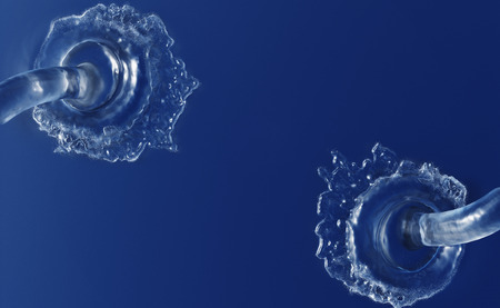 Two Large Water Jets start splashing in a quiet blue Liquid with small waves 写真素材