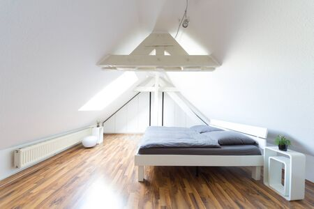 Wide angle view of modern, bright, puristic attic bedroom with double bed and gray bedclothes