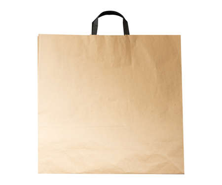 Kraft paper bag on dark wooden background Foto de archivo