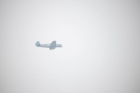 Propeller plane flying in the foggy sky over the sea