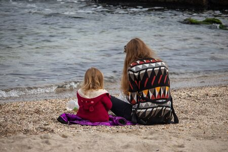 Girl with her mother on the sand by the water in autumn at sea Stockfoto - 133461005