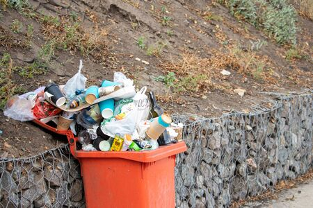Overcrowded orange container with garbage on the beach by the sea - Ukraine- Odessa - 10.17.2019