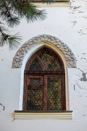 A window with a metal grille in an old house Stockfoto