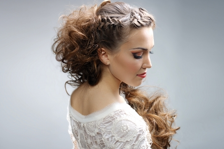 Beautiful woman with curly hairstyle against gray background photo