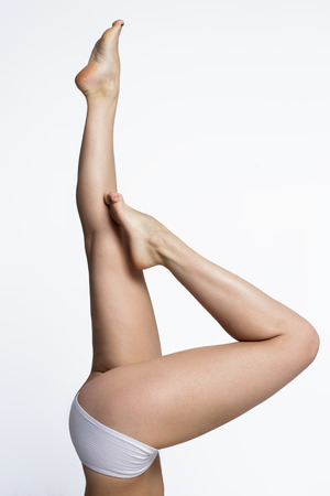 Waxing woman smooth legs pointing up on a white  photo