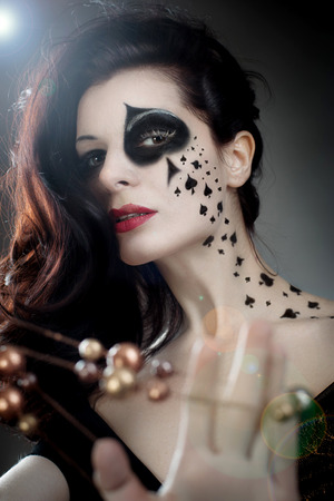 beautiful woman with make-up and body-art styled as playing card queens photo