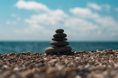 equilibrio: Piedras de equilibrio spa, sobre fondo azul mar tranquilo, imagen conceptual de relajación Foto de archivo