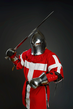 hauberk: Medieval knight with sword and shield against gray wall Stock Photo