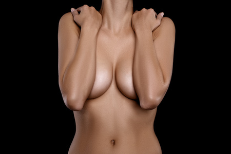 girl boobs: naked young woman covering her breast with hands against black background