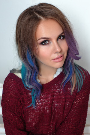 Fashion photo of a young woman with color hair. Close-up portrait photo