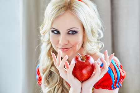 Positive woman holding an apple in her hands photo