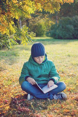 boy reading book in autumn Park Stock Photo