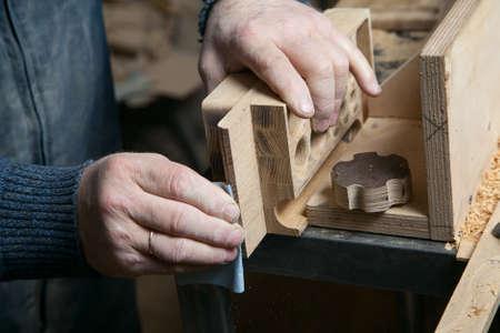 sandpaper: Man sandpaper grinds wood product in one studio