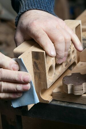 sandpaper: Hands male sandpaper grinds wood product in one studio