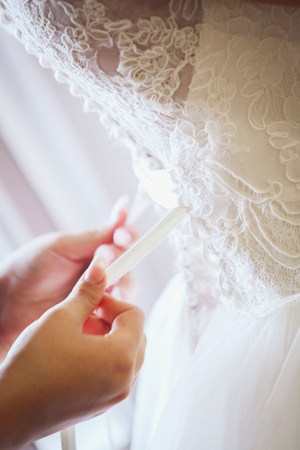 bridesmaid: Photo bridesmaid tying bow on wedding dress Stock Photo